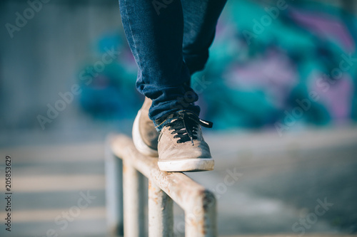 Photographie Legs walking on steel pipe with balance