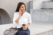 Happy business woman sitting outdoors with cup of coffee