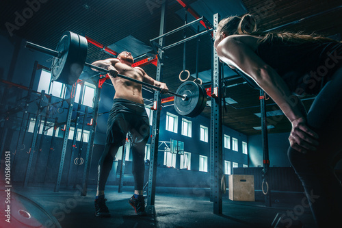 Fotografie, Obraz  Fit young man lifting barbells working out in a gym