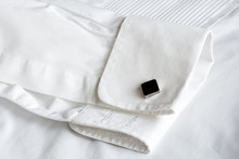 Black Cuff Links On The Sleeve Of The White Shirt