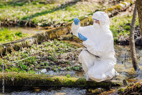 Valokuva  female scientist examining the liquid contents of a  test tube in the forest