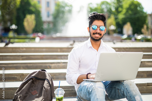 East Indian American College Student sits on stairs on