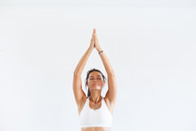 Charming Young Woman Instructor In Yoga Meditating With Closed Eyes Or Close-up Hands On White Background. Copyspace