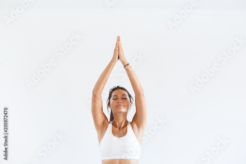 Staande foto School de yoga Charming young woman instructor in yoga meditating with closed eyes or close-up hands on white background. Copyspace