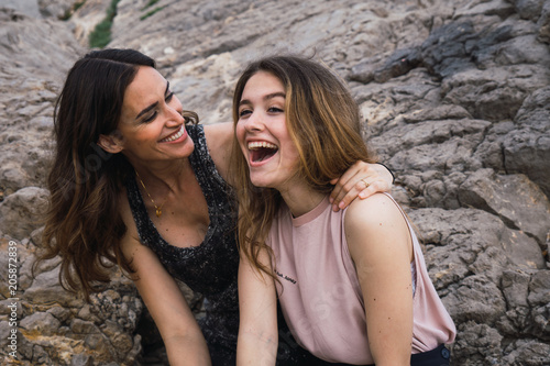 Two young friends on big rock background