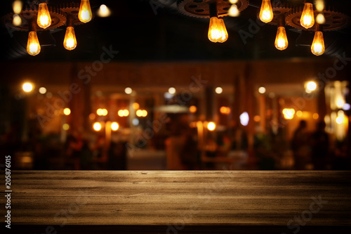 Poster Restaurant Image of wooden table in front of abstract blurred restaurant lights background.