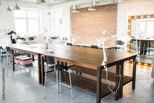 Modern atelier interior with wooden workstation in foreground and sewing dummies Canvas Print