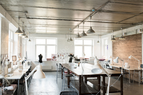 Wide angle shot of modern atelier interior with wooden workstation in foreground Canvas Print