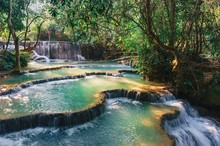 Beautiful Waterfall Kuang Si In Sunlight.Landscape With Amazing Turquoise Water Of Kuang Si Cascade Waterfall At Deep Tropical Rain Forest.Landscapes And Places Of Rest In Laos.