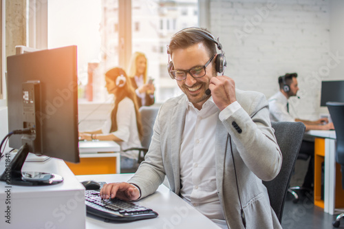 Smiling businessman on the phone with headset talking with client