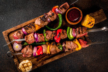 Fresh, Home-cooked On The Grill Fire Meat Beef Shish Kebab With Vegetables And Spices, With Barbecue Sauce And Ketchup, On A Dark Background On A Wooden Cutting Board Above Copy Space