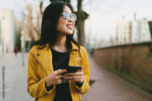 Valokuvatapetti Half length portrait of a beautiful smiling asian femalein a sunglasses with long dark hair wearing yellow leather jacket reading emails on a mobile phone while standing on blurred street background