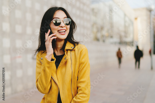 Fotografía  Smiling asian woman with long dark hair in sunglasses talking by a smartphone while walking the city street