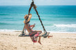 woman relax sitting and playing mobile on line on wooden swing under plam tree at sunny on the island, summer time vacation and weekend relax funny happy time
