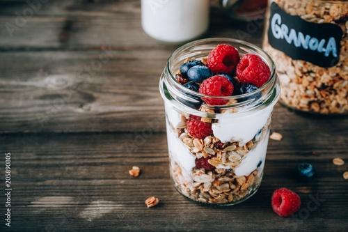 Deurstickers Akt Healthy blueberry and raspberry parfait with greek yogurt in glass mason jar on wood background