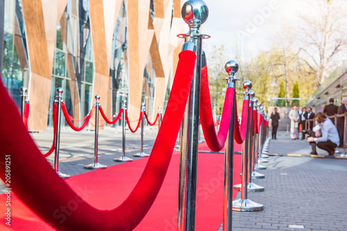 Fotografía Close up red carpet ceremony with selective focus on the stanchions and the ropes with blurred guests and photographer background