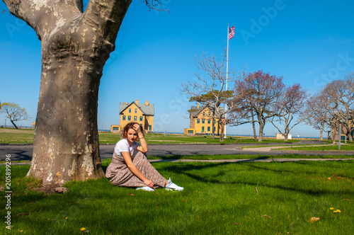 Photo  Beautiful woman is sitting in the park near the tree.