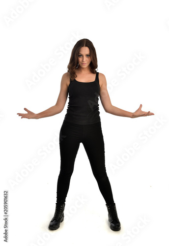 full length portrait of brunette girl wearing black singlet, jeans jeans and boots. standing pose, isolated on white studio background. Wall mural