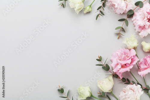 Foto auf Leinwand Blumen Floral border of beautiful flowers and green eucalyptus leaves on gray table top view. Flat lay composition.
