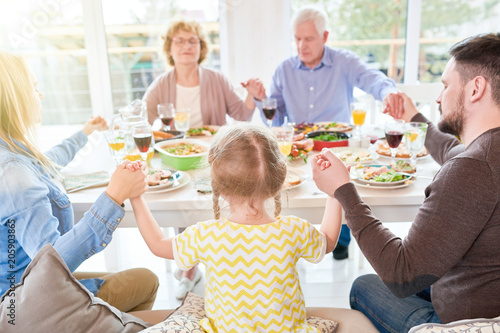 Fotografie, Obraz  Portrait of big happy family saying grace at dinner holding hands during festive