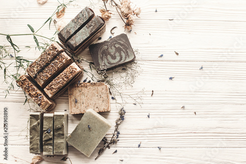 natural soap. handmade herbal soap with wildflowers, healing flowers, mint, lavender, space text. eco natural product for skin care. soap on white rustic background with dried herbs, flat lay.