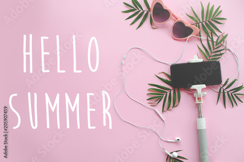 Photo sur Aluminium Magasin de musique Hello Summer text on stylish pink sunglasses, phone on selfie stick, headphones, and green palm leaves on pink background. stylish summer vacation flat lay. hello holidays