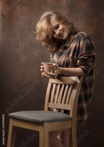 Fotobehang Koffiebonen Pretty woman with long blonde hair in brown plaid shirt holds brown cup.