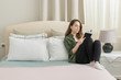 Portrait of a woman reading a book sitting on her bed.