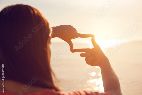 Future planning, Close up of woman hands making frame gesture with sunrise on sea summer, Female capturing the sunrise, sunlight outdoor Canvas Print