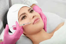 Studio Photo Of Cosmetological Lips Enlargment Process. Medical Injection For Plump, Soft, Large Lips. Young Model With Beatiful Face Wearing White Headbandage. Profassional Wearing Pink Gloves.