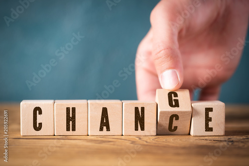 Fotografía  Hand flips one of six cubes with letters, turning the word change to chance