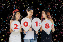 Group Of Beautiful Young Asian People Celebrating New Year's Eve,and Holding Balloons Numbers 2018 Written On Them.happy And Funny Concept