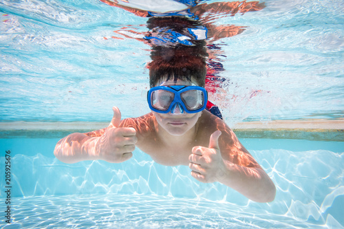 Boy in mask dive in swimming pool
