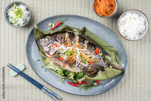 Traditioneller Thai gegrillter Tilapia Fisch mit Chili und Gemüse als Draufsicht auf einem Teller mit Bananenblatt