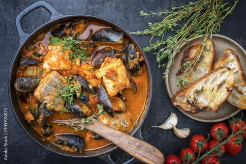 Traditionelle französisch korsische Fischsuppe mit Muscheln und Knoblauch Baguette als Draufsicht in einem Topf