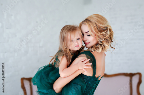 Tablou Canvas Portrait of a beautiful young mother with a cute blonde daughter sitting in white interior dressed in elegant green dresses