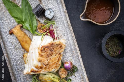 Modern japanisch gebratenes Kabeljau Fisch Filet mit with Pak Choi und Sushi als Draufsicht auf einem Teller