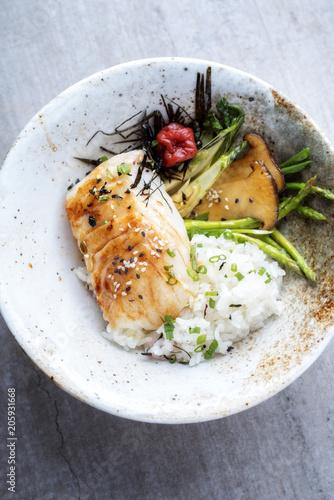 Modern japanisch gebratenes Kabeljau Fisch Filet mit grünen Spargel  und Reis als Draufsicht in einer Schale
