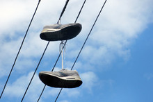 Two Old Sneakers Hang On Electric Wires. The Concept Is Time For A Vacation