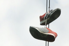 Two Old Sneakers Hang On Elect...