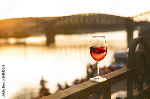 Photo  Glass of red wine on a railing with sunset in a Prague city