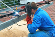 Man at work: welder worker on constructiion site working with metal construction