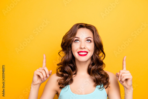Portrait of pretty trendy girl with modern hairdo pointing two forefingers up showing copy space empty place isolated on yellow background, advertisement concept