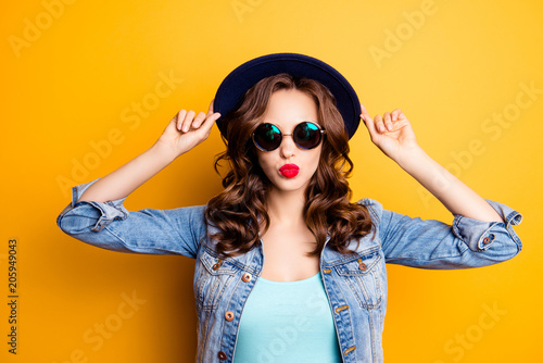 Fotografering  Portrait of cool charming girl holding hat on her head sending kiss with pout li