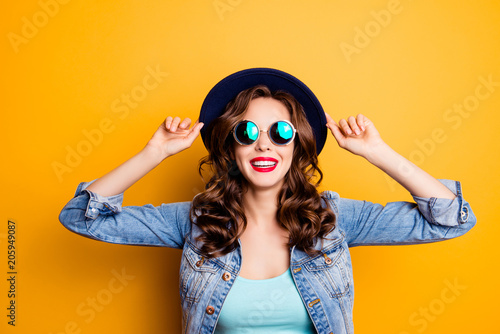 Valokuva  Portrait of toothy cheerful tourist in perfect good mood holding hat on head with hands having beaming smile fashionable look isolated on yellow background