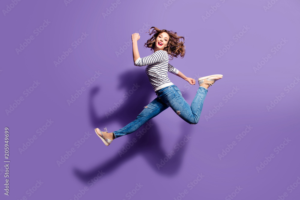 Fototapety, obrazy: Portrait of sportive active girl in motion jumping over in the air isolated on violet background having perfect stretching looking at camera