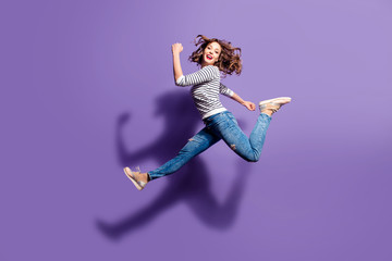 Portrait of sportive active girl in motion jumping over in the air isolated on violet background having perfect stretching looking at camera