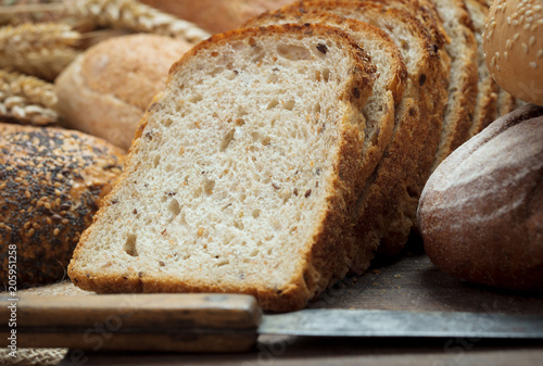 Poster Brood heap of fresh baked bread with knife on wooden background