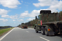 A Convoy Of Military Trucks While Passing The Highway