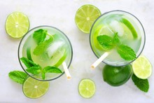 Two Glasses Of Summer Limeade With Mint. Top View On A White Marble Background.